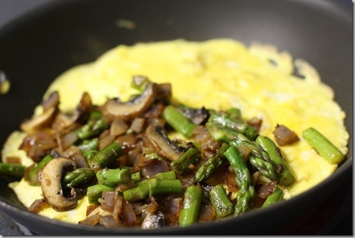 skillet with open omelete with asparagus and mushrooms