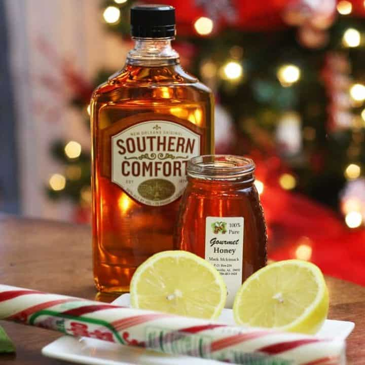 Bottle of Southern Comfort, a jar of honey, a halved lemon, and a peppermint stick.