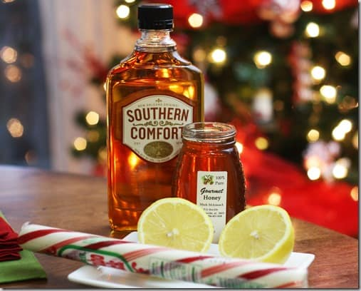 A jar of honey, bottle of southern comfort, sliced lemon, and peppermint stick.