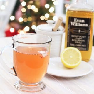 A glass cup with peppermint whiskey honey and lemon on a white tray with a bottle of whiskey and half cut lemon on a plate.